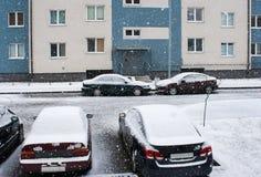 在房子附近的四辆汽车雪的 免版税库存图片