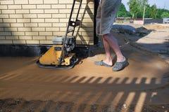 在房子附近的建造者猛撞的沙子建造场所的 图库摄影