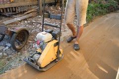 在房子附近的建造者猛撞的沙子建造场所的 免版税图库摄影