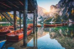在房子附近的木小船在日出的Braies湖 库存图片