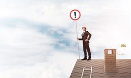 在房子顶面显示的标志的商人与惊叹号 混合 免版税库存照片