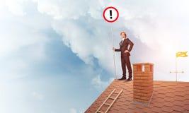 在房子顶面显示的标志的商人与惊叹号 混合 库存图片