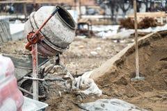 在房子建造场所的工业水泥搅拌车机器 混凝土搅拌机、沙子和工具 免版税库存照片