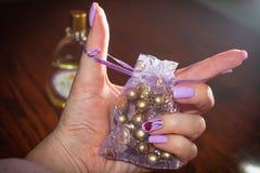 在手上在紫胶的颜色的淡紫色袋子钉牢 免版税库存图片