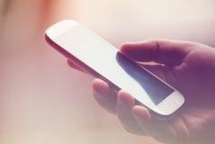 在手上拿着智能手机 免版税库存照片