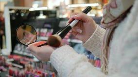 在手上搽粉,掠过为组成,并且镜子,有明亮的构成的性感的金发碧眼的女人,美容院的美容师做 影视素材
