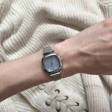 在手上的妇女的手表在毛线衣的背景 免版税图库摄影