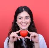 在手上的愉快的妇女画象拿着心脏反对红色backg 免版税库存图片