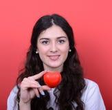 在手上的愉快的妇女画象拿着心脏反对红色backg 免版税图库摄影