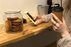 在手上的特写镜头有电话的 女孩喝在咖啡馆的咖啡 免版税图库摄影