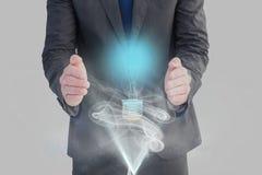 在手上的电灯泡反对灰色背景 库存图片
