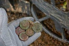 在手上的老硬币在金属探测器上的手套盘绕 库存图片