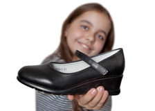 在手中举行在一双黑鞋子前面的快乐的女孩 免版税图库摄影