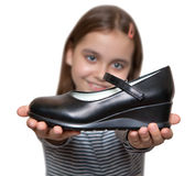 在手中举行在一双黑鞋子前面的愉快的女孩 免版税库存图片