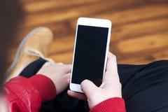 在手中举行在立姿的白色智能手机 免版税库存图片