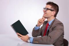 在手中作白日梦与书的年轻商人的边 免版税库存图片