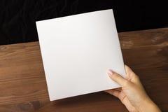 在手中倒空笔记的白皮书,笔记本,日志,小册子,组织者在一张木桌上 库存图片