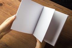 在手中倒空笔记的白皮书,笔记本,日志,小册子,组织者在一张木桌上 免版税库存照片