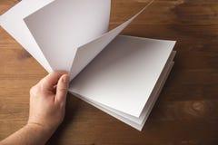 在手中倒空笔记的白皮书,笔记本,日志,小册子,组织者在一张木桌上 免版税图库摄影