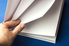 在手中倒空笔记的白皮书,笔记本,日志,小册子,组织者蓝色背景的 免版税库存图片