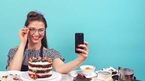 在手中做selfie用杯形蛋糕的逗人喜爱的酥皮点心女孩 股票录像