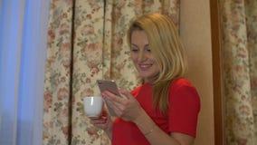 在手中关闭美好的年轻白种人妇女读书正文消息画象在手机的有咖啡的 影视素材