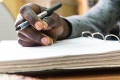 在手中写的非洲人候宰栏在空白的白皮书 免版税库存图片