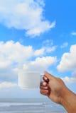在手中加奶咖啡杯子在蓝天背景 图库摄影