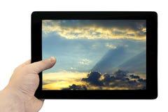 在手中压片个人计算机有美丽的蓝天的有在被隔绝的屏幕上的金黄日落背景 库存图片