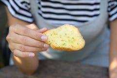 在手中吃蒜味面包的女孩 库存图片
