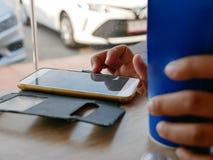 在手中坐和使用智能手机生活方式在有一个杯子的一家便当餐馆碳酸化合的汽水 免版税库存照片