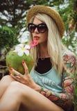 在手中坐在一个热带庭院里的草帽和太阳镜的美丽的年轻白肤金发的行家用椰子 雨 免版税库存图片