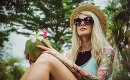 在手中坐在一个热带庭院里的草帽和太阳镜的美丽的年轻白肤金发的行家用椰子 雨 免版税库存照片