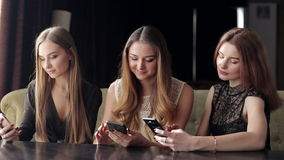 在手中坐在与电话的一个咖啡馆的三个女孩,电话瘾 影视素材