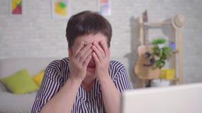 在手中坐在有万一银行卡的一台膝上型计算机的沮丧的妇女 股票录像