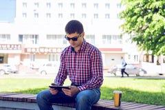 在手中坐在有片剂的在玻璃的公园,夏天和一件衬衣的人在森林户外,读社交 库存照片