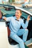 在手中坐在有钥匙的一辆敞篷车汽车的妇女 库存照片