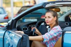 在手中坐在有钥匙的一辆敞篷车汽车的少妇 免版税图库摄影