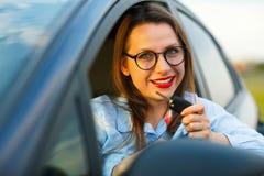 在手中坐在有钥匙的一辆汽车的年轻俏丽的妇女 免版税库存图片