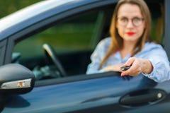 在手中坐在有钥匙的一辆汽车的年轻俏丽的妇女 免版税库存照片
