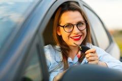 在手中坐在有钥匙的一辆汽车的年轻俏丽的妇女 免版税图库摄影
