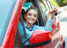 在手中坐在有钥匙的一辆汽车的年轻快乐的妇女 库存图片