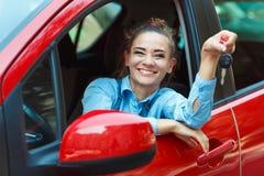 在手中坐在有钥匙的一辆汽车的年轻快乐的妇女 免版税库存照片