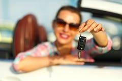 在手中坐在有钥匙- conce的一辆敞篷车汽车的妇女 免版税库存图片