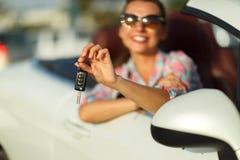 在手中坐在有钥匙- conce的一辆敞篷车汽车的妇女 免版税图库摄影