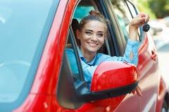 在手中坐在有钥匙- concep的一辆汽车的年轻快乐的妇女 库存照片