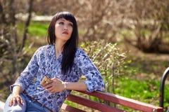 在手中坐长凳在有电话的公园和调查距离的美丽的亚裔女孩 库存照片