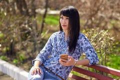 在手中坐长凳在有电话的公园和调查距离的美丽的亚裔女孩 图库摄影