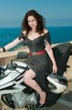 在手中塑造在有盔甲的一辆摩托车反对海 库存图片