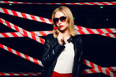 在手中塑造性感的白肤金发的女孩画象用糖果和在警告磁带背景的红色嘴唇  免版税图库摄影